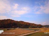 紅葉の山と農村 微速度撮影 紅葉した山と稲刈りを終えた農村の風景